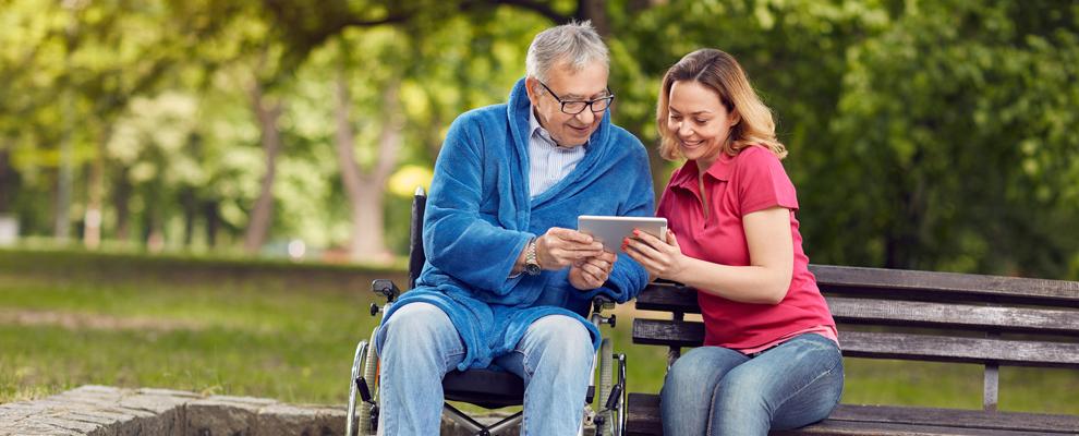 Mann im Rollstuhl hält ein Tablet und spricht mit Betreuerin